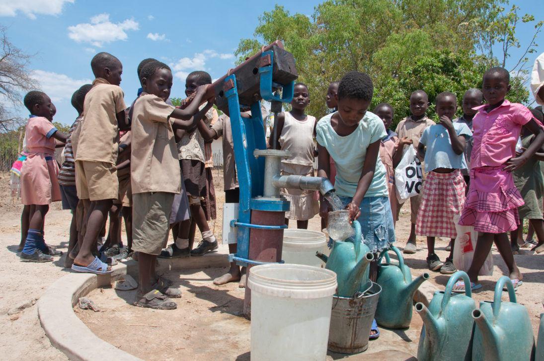 Kids filling water buckets.